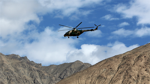 Transport helicopter flies over mountains